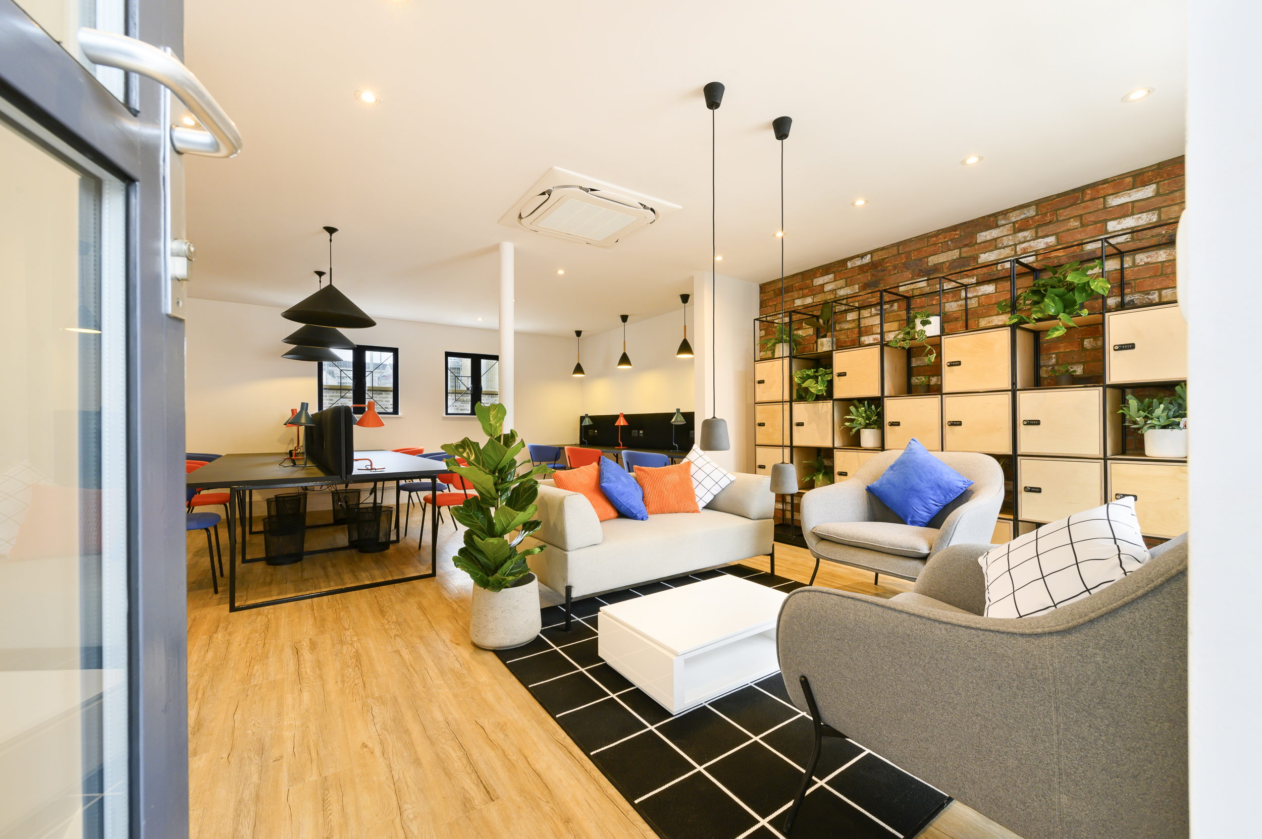 A colourful co-working space at Worlds End Studios with seating, lockers and spacious desks.