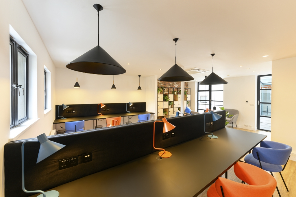 A colourful co-working space at Worlds End Studios with large spacious desks, all with individual lighting and power sockets.