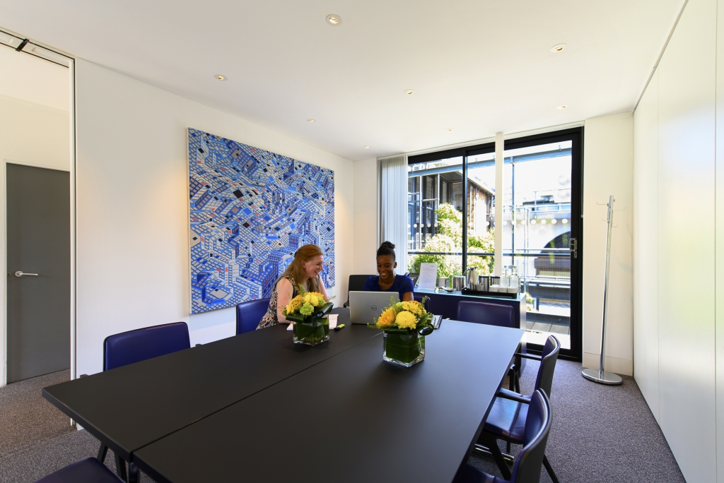A standard meeting room with two females talking over a laptop.