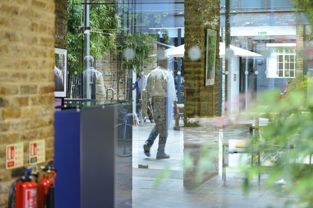 Looking through the reception area at Worlds End Studios from one courtyard to another with reflections of a man.