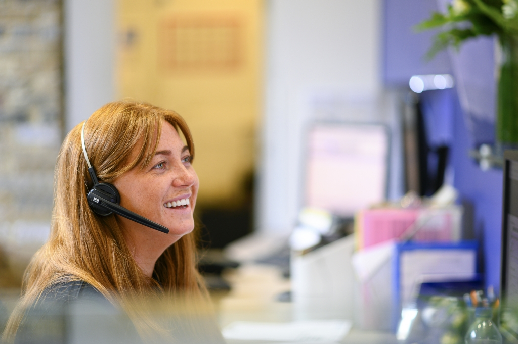 A smiling woman with a headset whilst sat at the Frontdesk in Worlds End Studios.