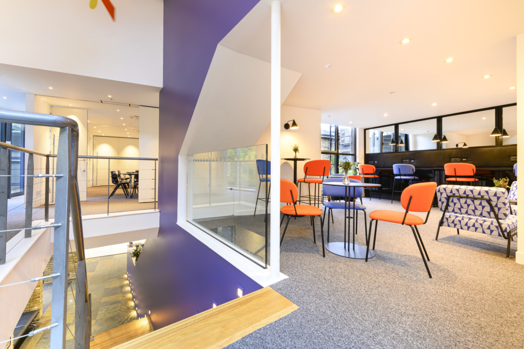 Bright and airy space at the top of the stairs. Orange and blue chairs on the inner side of a crisp purple wall