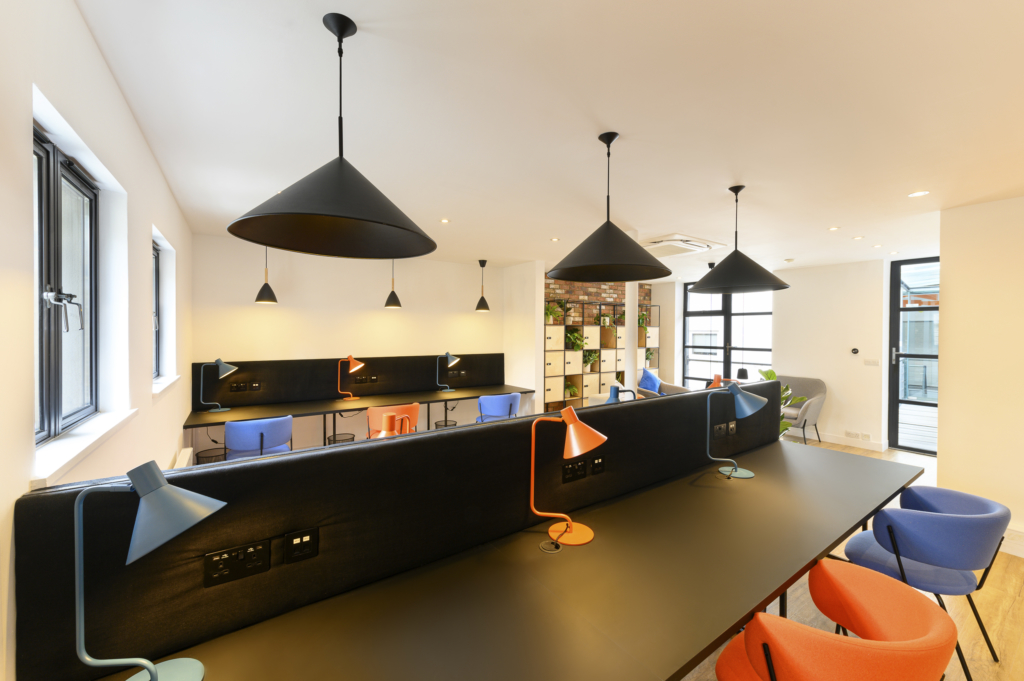 Worlds End Studios Co working space, blue and orange chairs with black table tops
