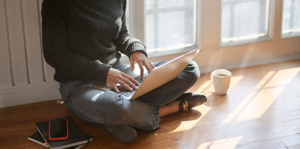 Woman sitting with laptop on Floor at Home